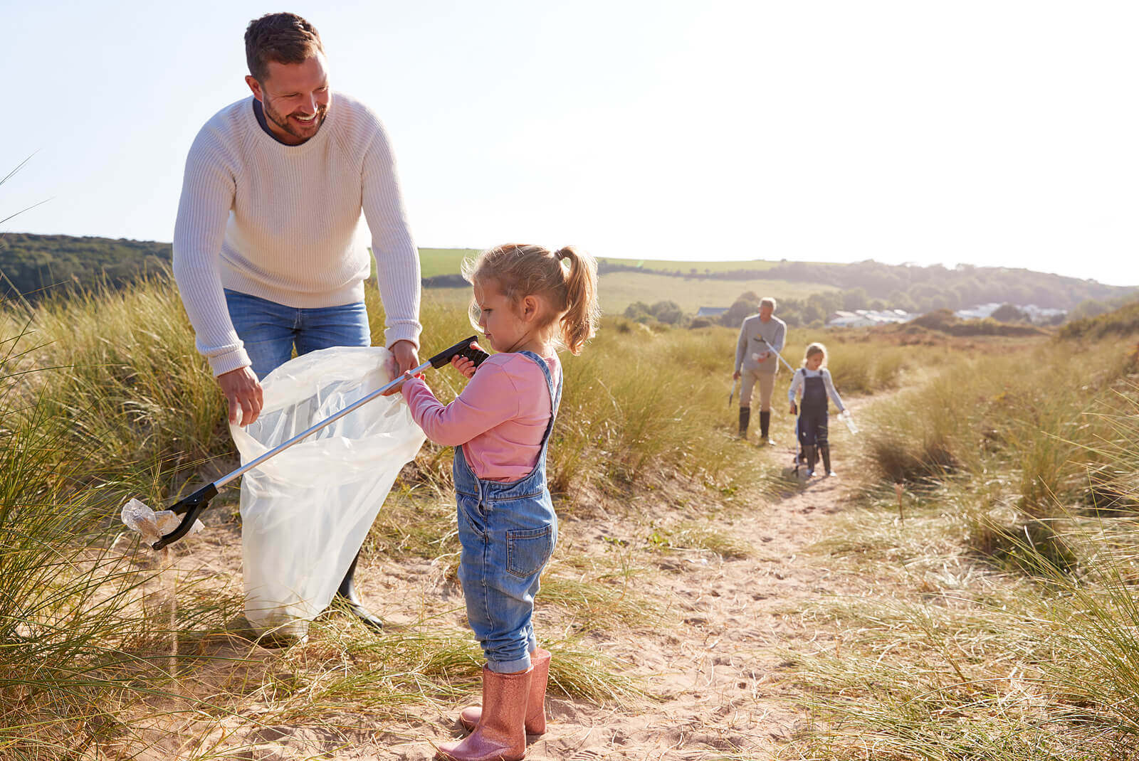 A family litter picking on a beach dune, father and daughter in foreground