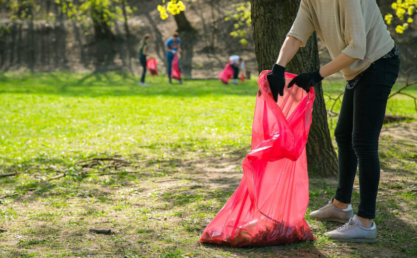 A volunteer litter picking in a park with a red bag