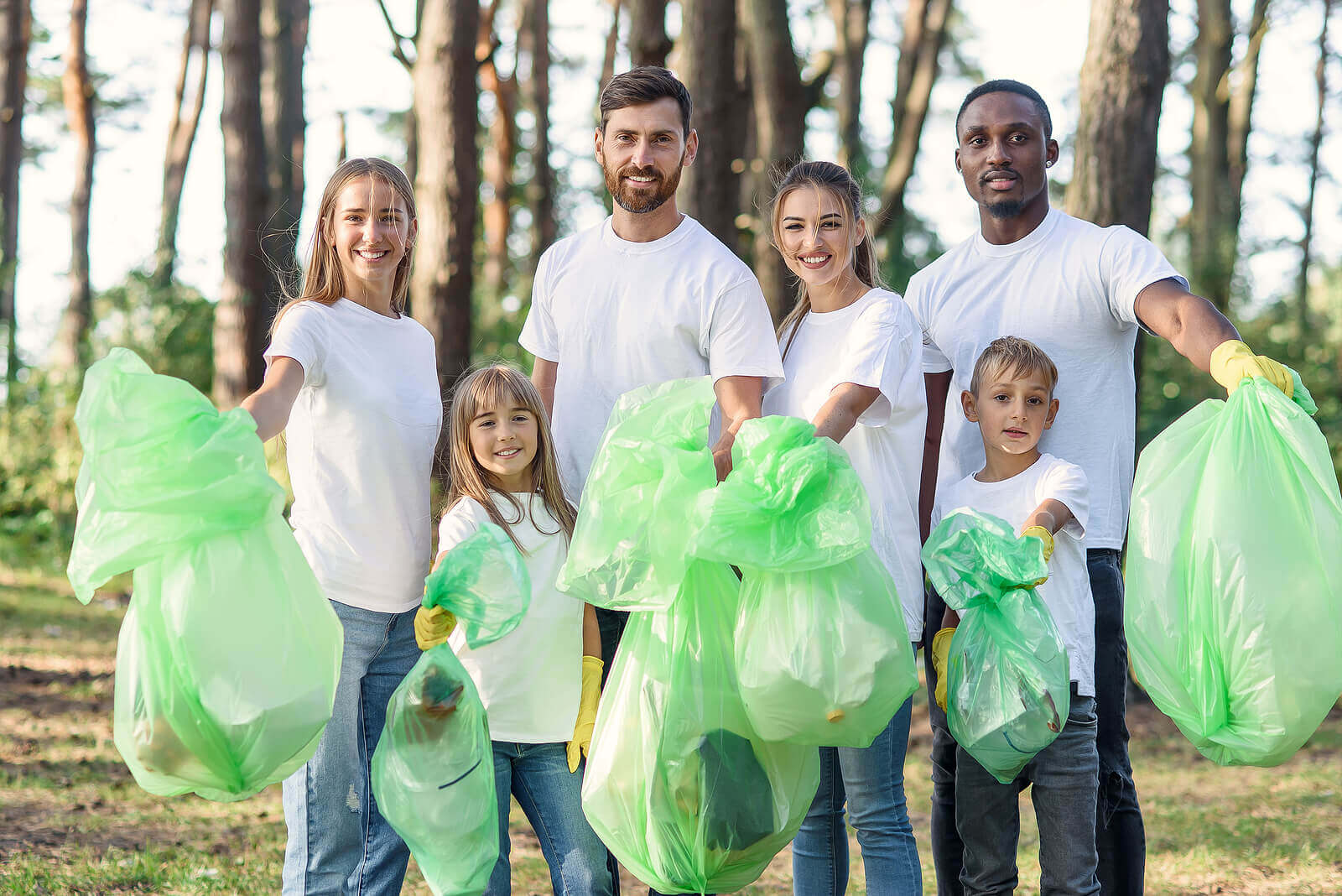 A group of volunteer litter pickers holding green bags of rubbish