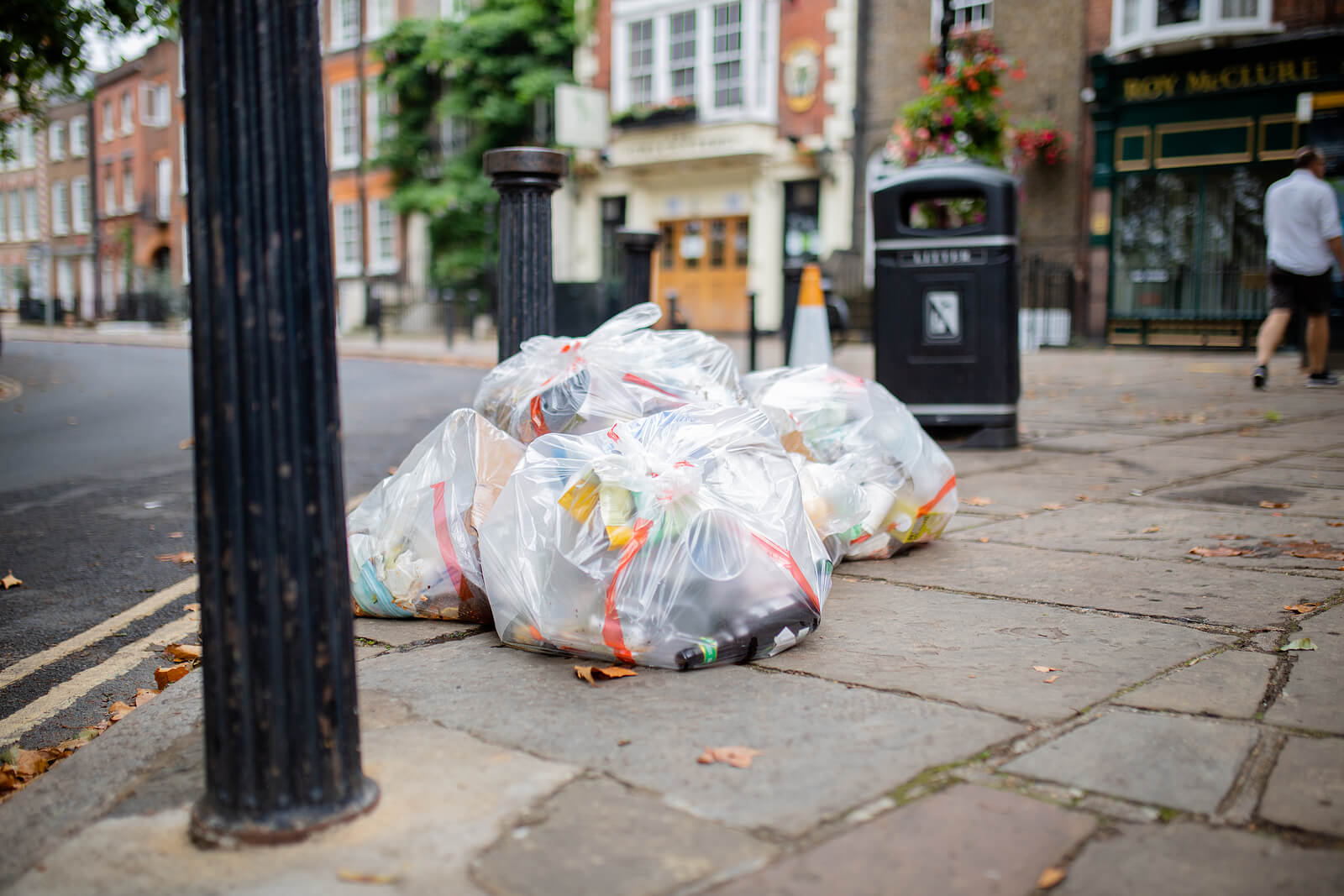 Bags of litter and rubbish collected on a street in a town centre