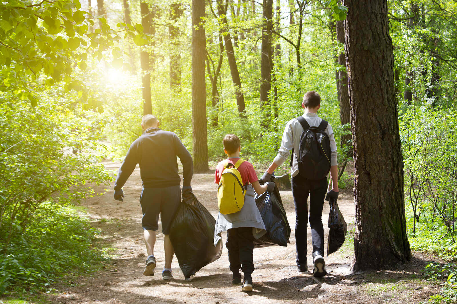 A family carrying bags of rubbish after litter picking in the woods