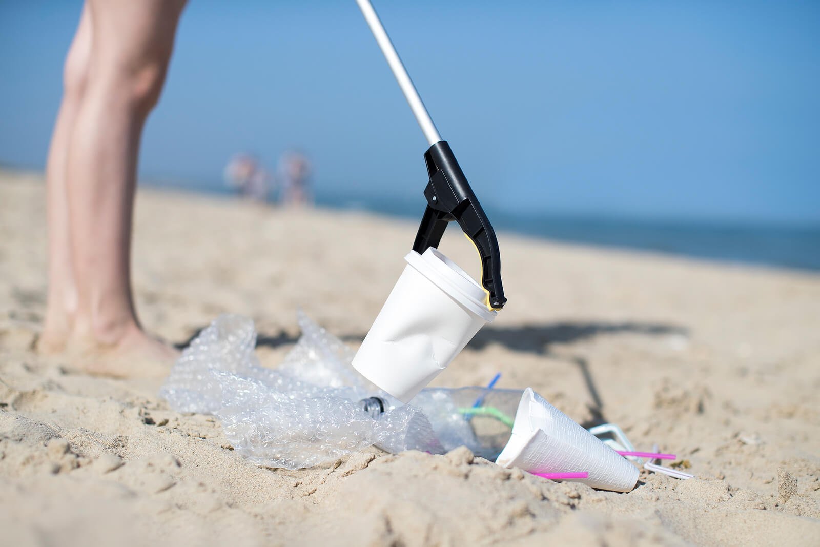 Someone litter picking on a beach, using a litter picker to pick up a coffee cup
