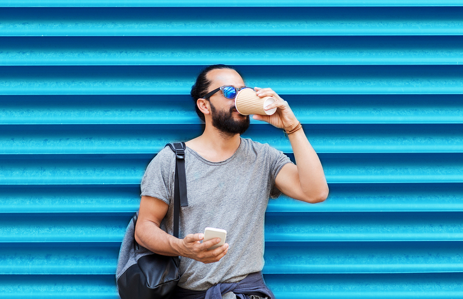 Man drinking from disposable coffee cup