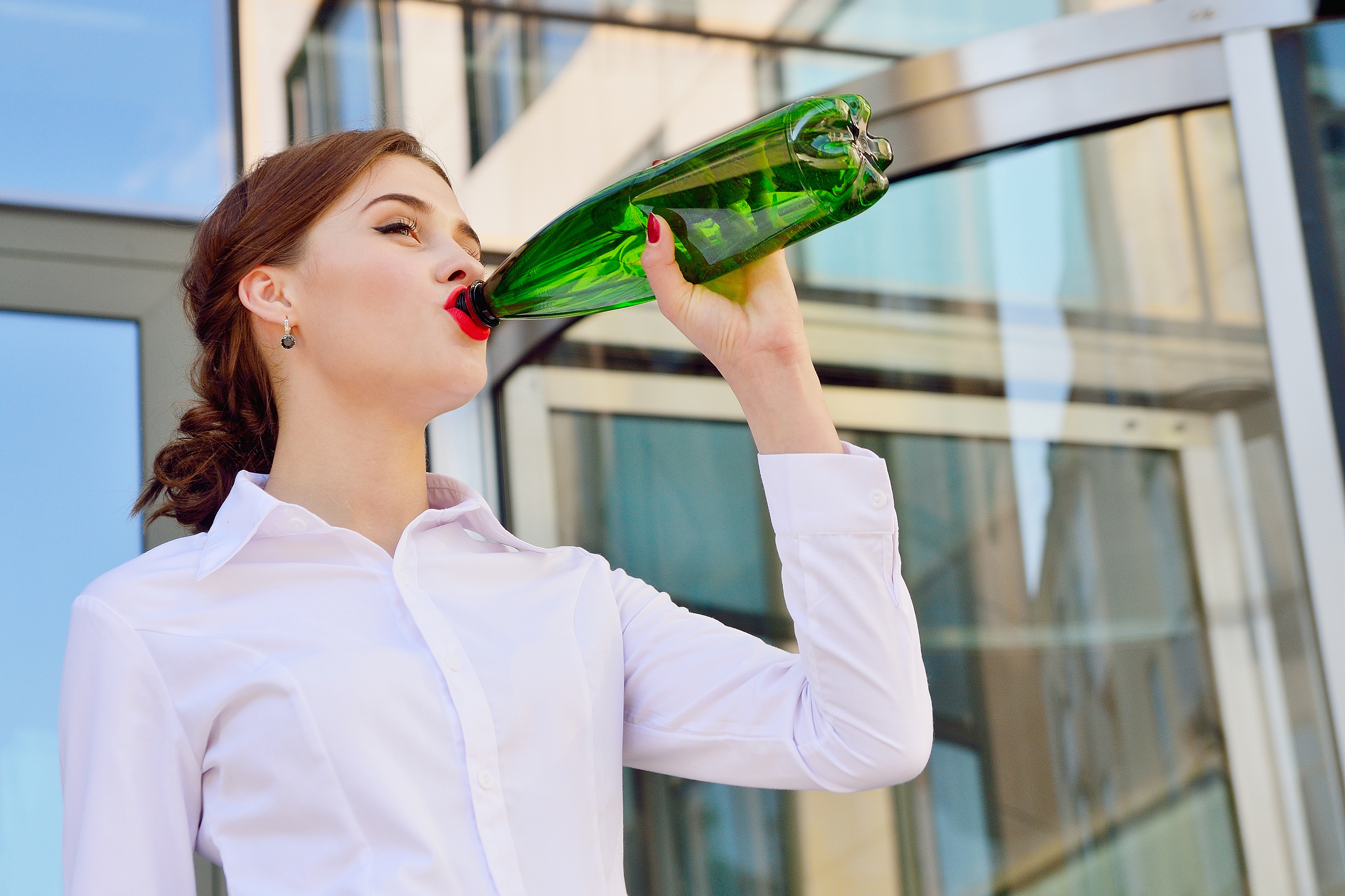 Business employee drinking from plastic bottle