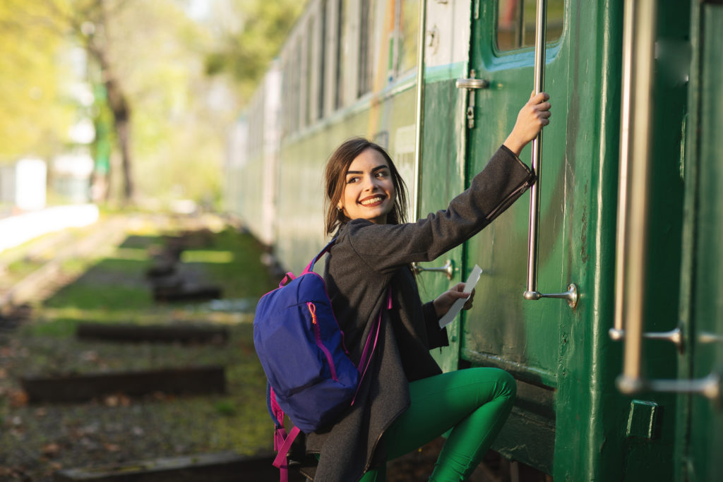 Woman boarding a train, which is eco-friendly