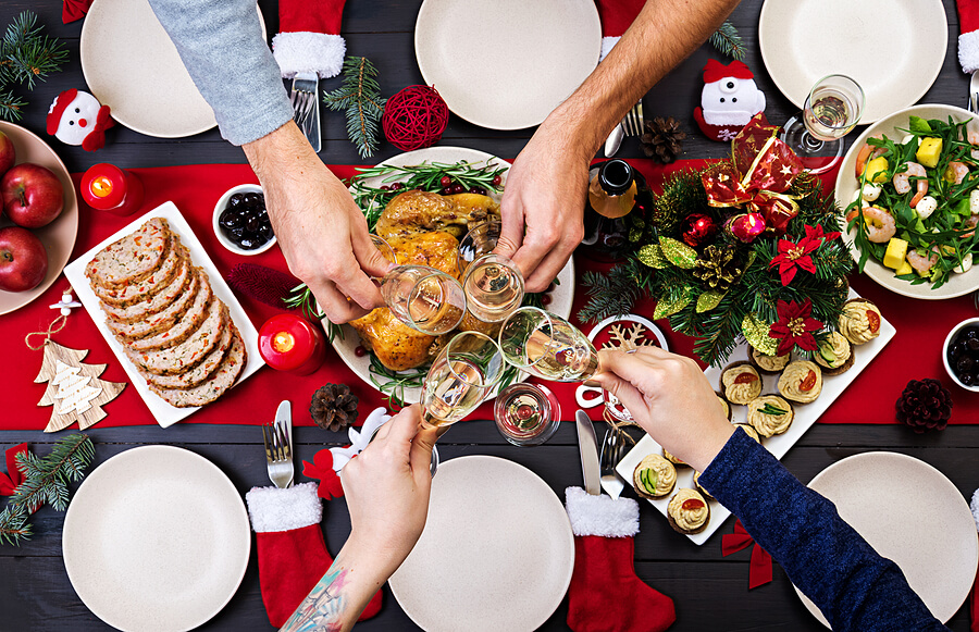 Family saying cheers with champagne flutes over table of Christmas dinner
