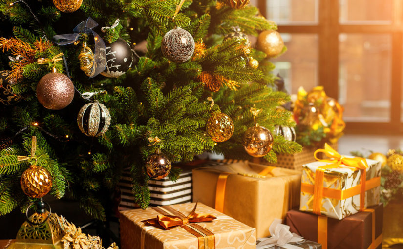 Christmas tree with gold decorations and wrapped gifts beneath it