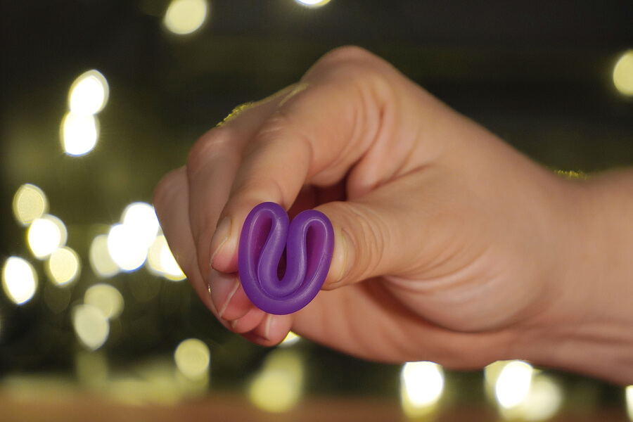 a purple menstrual cup being held in a c-fold