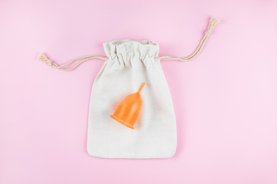 an orange menstrual cup sat on top of a cotton storage bag