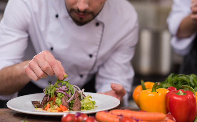 a chef finishing a dish in a restaurant