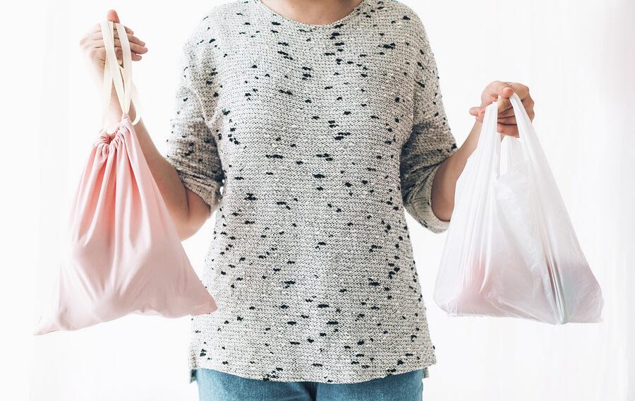 woman holding plastic bag and reusable shopping bag