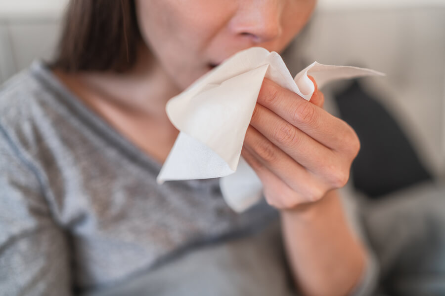 coughing in a tissue with coronavirus symptoms