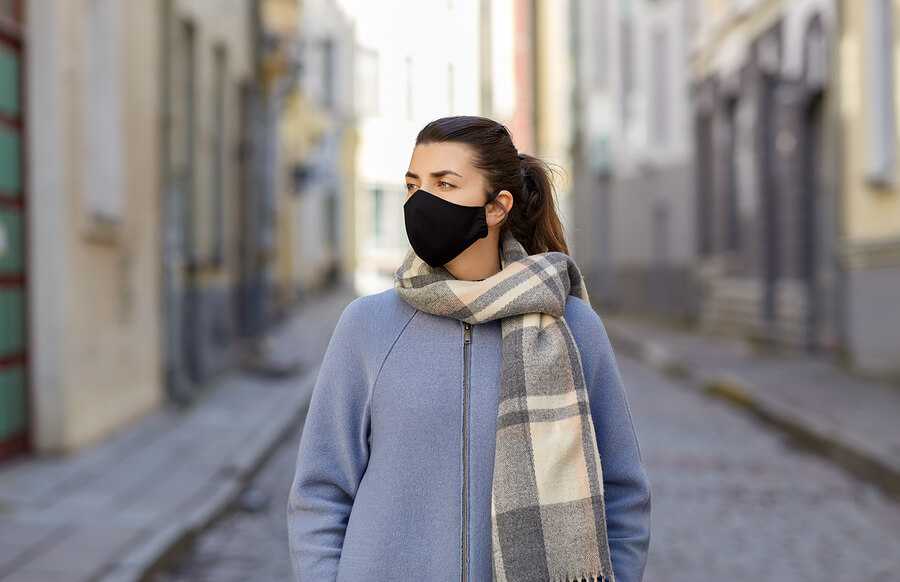 woman wearing coat and reusable fabric face mask