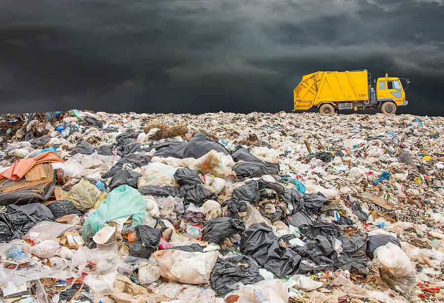 Lanfill cubierto de basura con un cielo oscuro y un camión pasando.