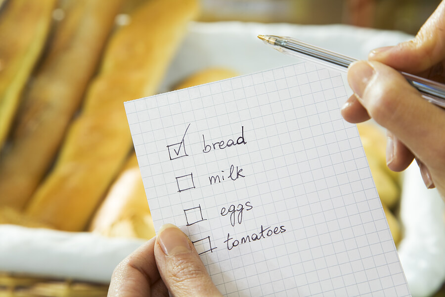A shopping list with bread, milk, eggs and tomatoes.
