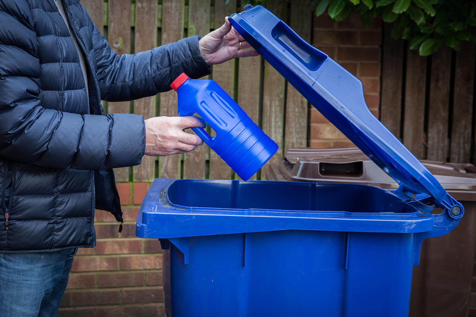 A man recycling a plastic bottle in a wheelie bin