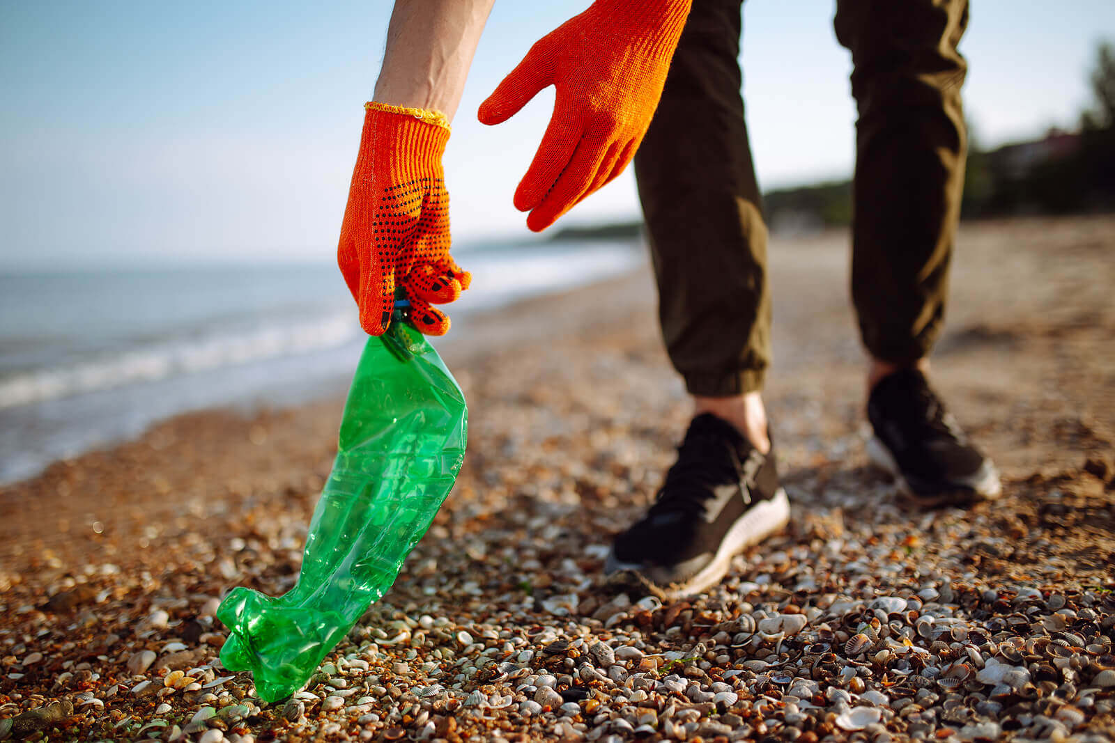 A person litter-picking on the beach, picking up a green plastic bottle with orange gloves