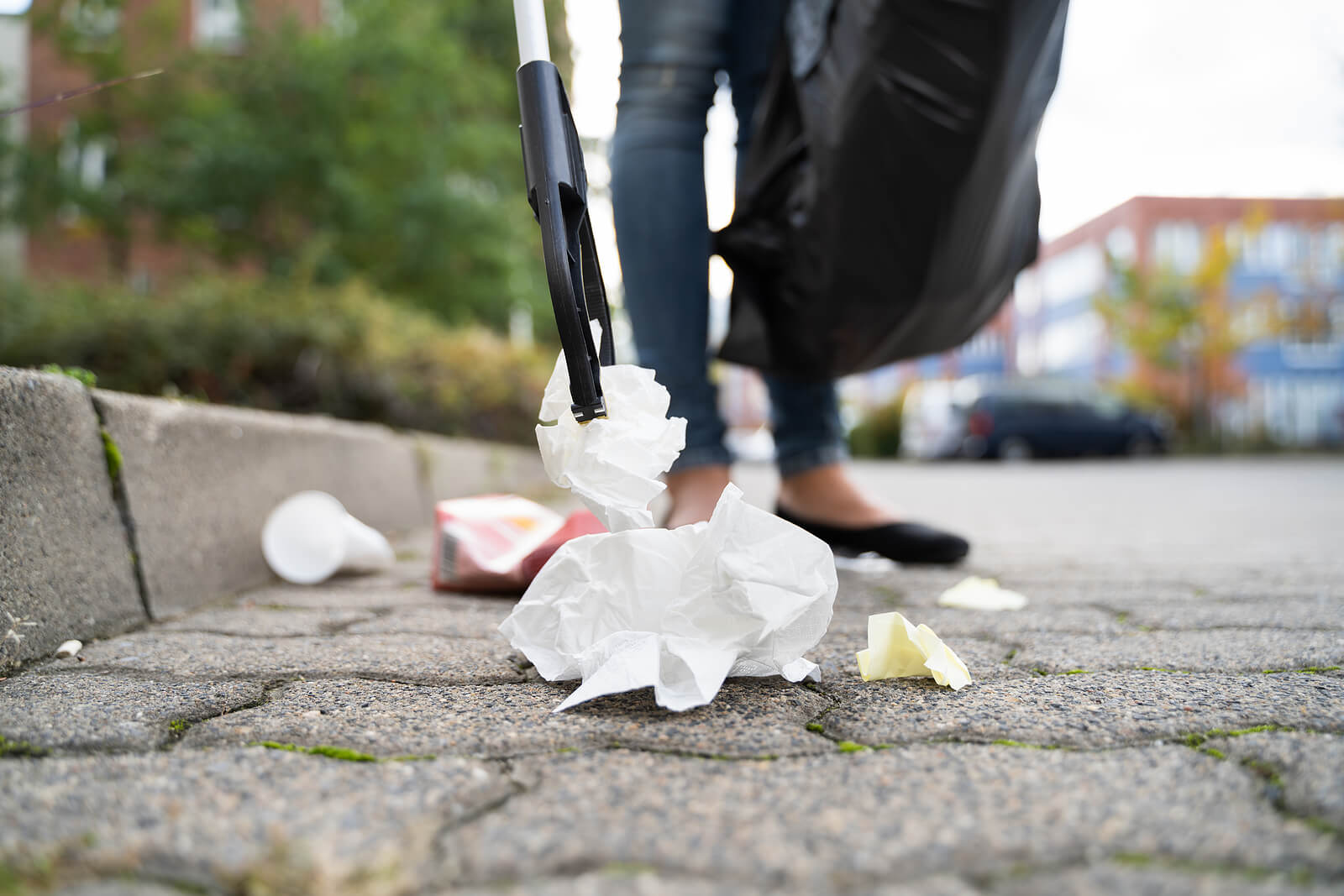 A street-level view of a woman litter-picking rubbish in the street