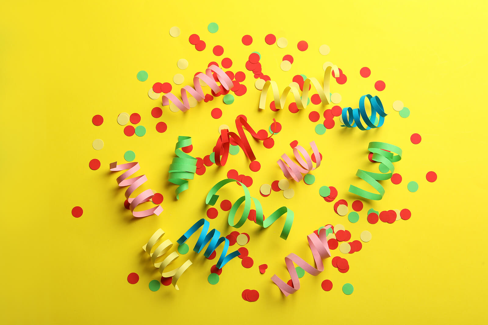 Paper streamers and confetti on a yellow background