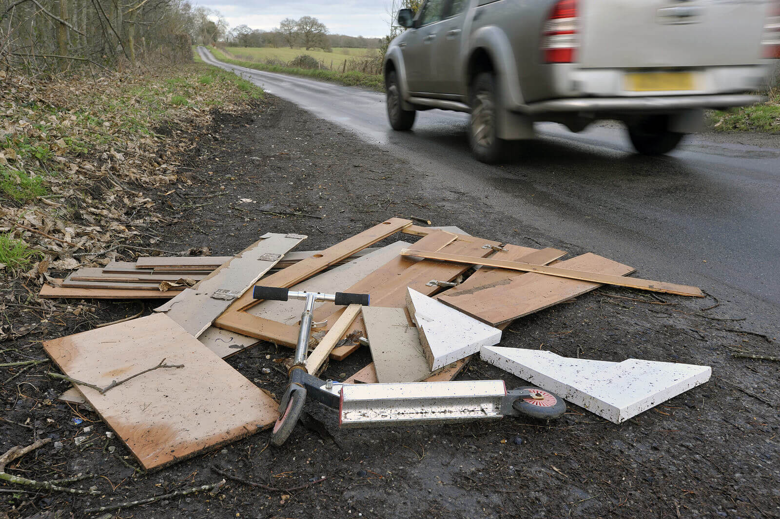 Fly-tipped household waste at the roadside with a van driving off