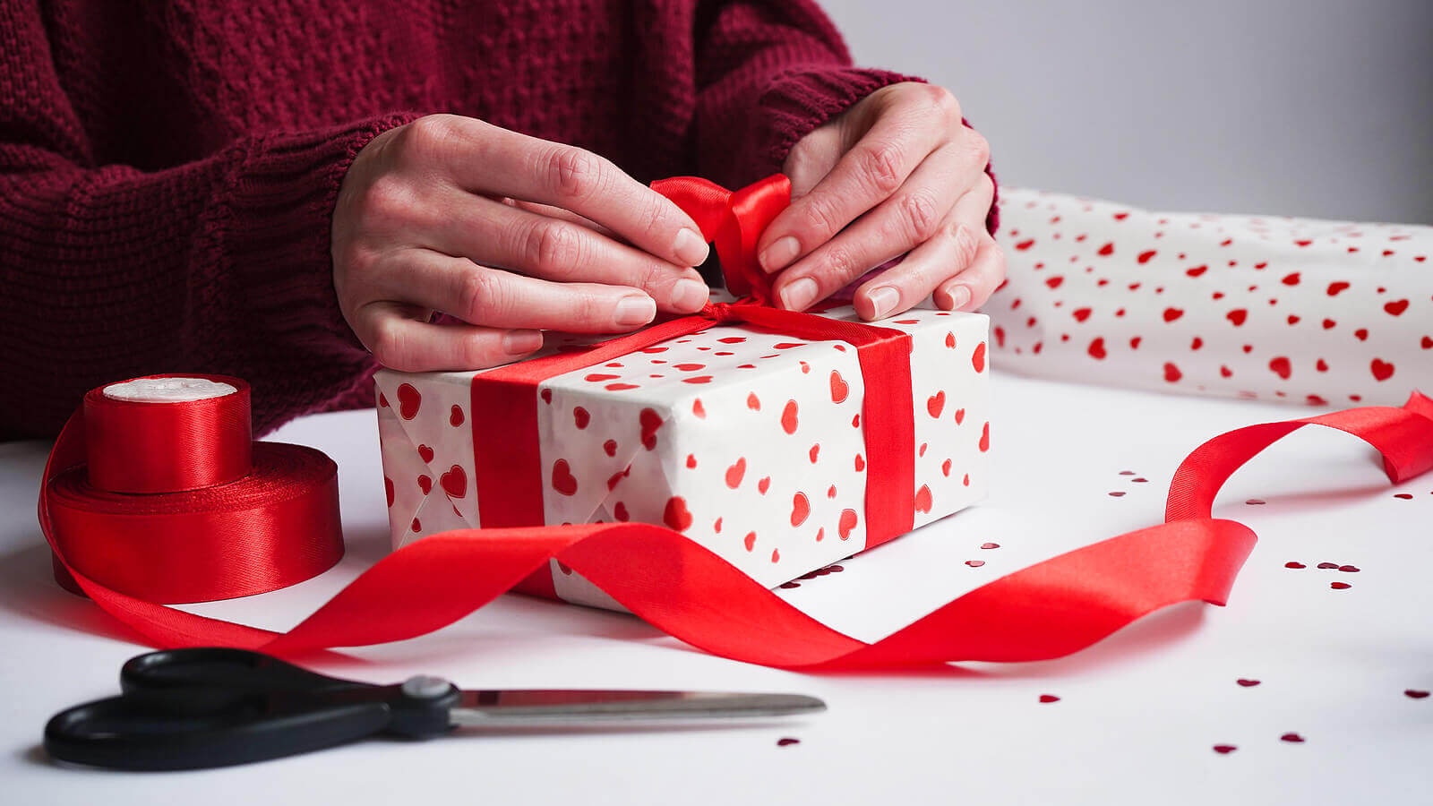 Hands tying a red bow on a wrapped Valentine's Day gift