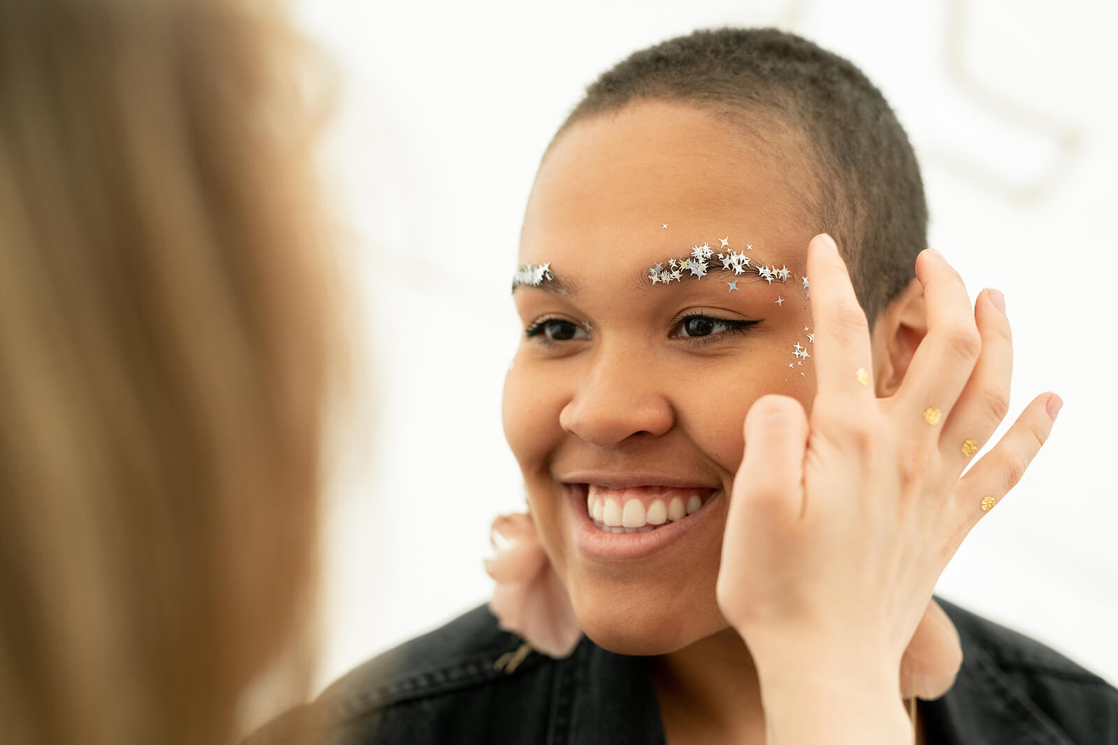 A Black woman having star-shaped glitter applied to her face