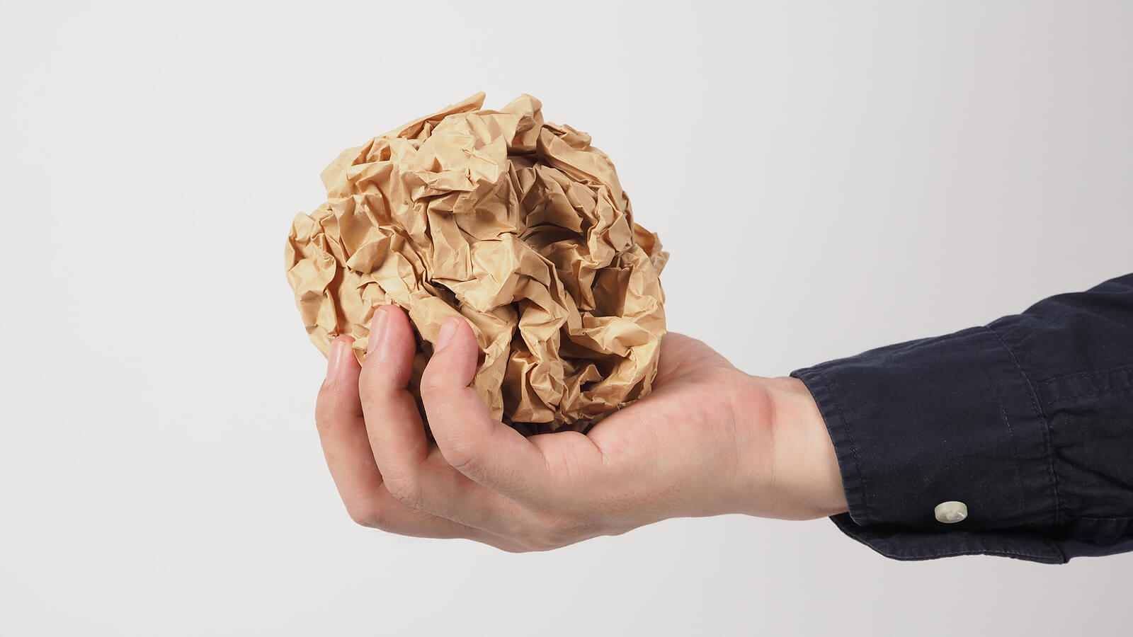 A hand holding a crumpled ball of brown gift wrap paper