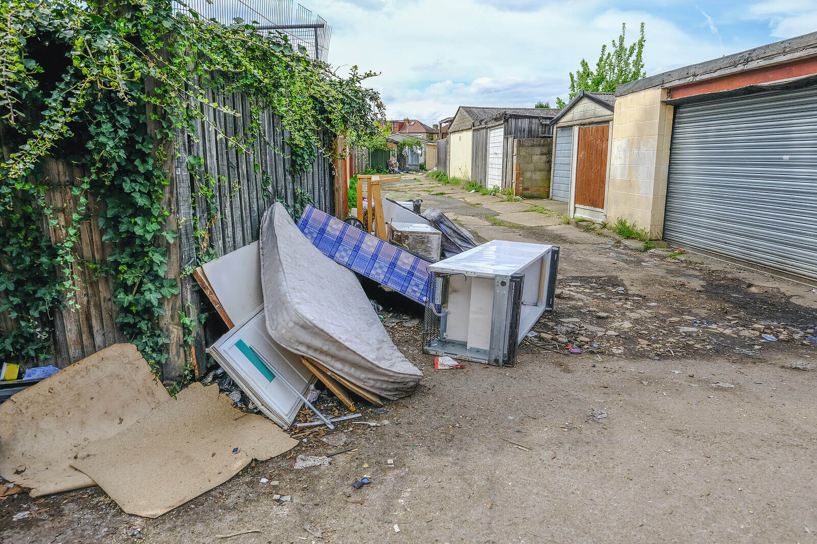 Fly-tipped waste in an urban alleyway next to garages