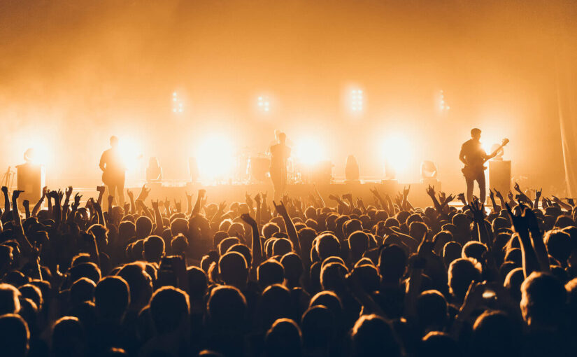 The silhouette of a music festival crowd while a band performs on stage