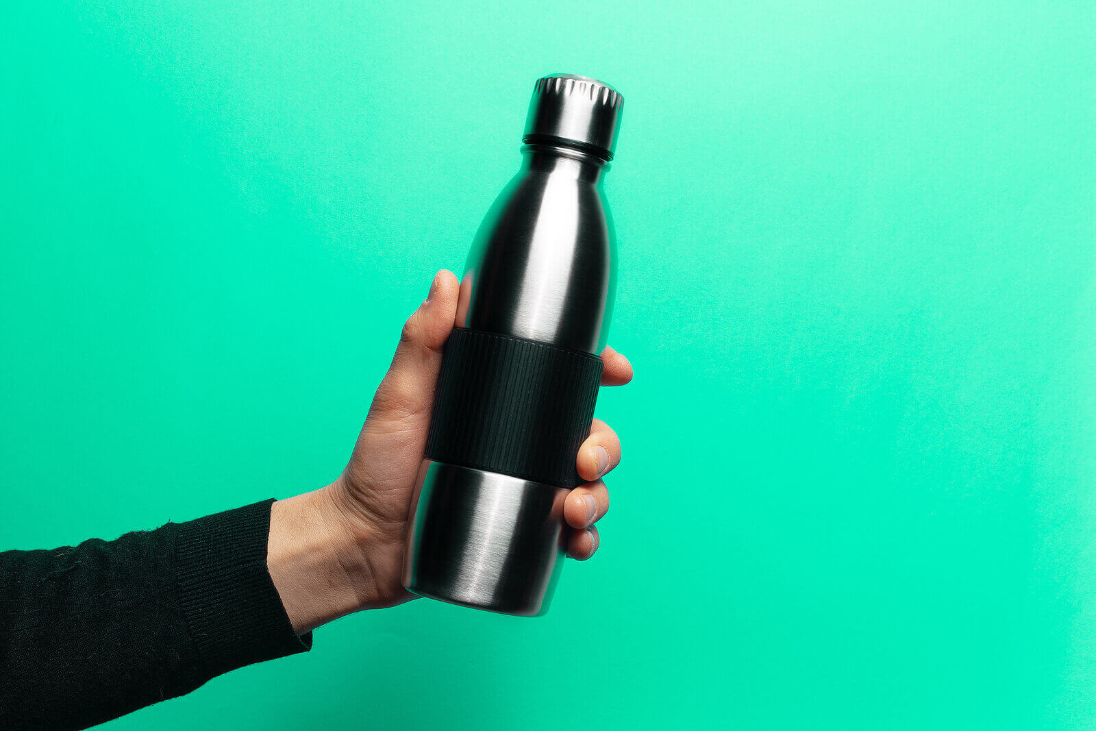 A hand holding a reusable water bottle against a green background