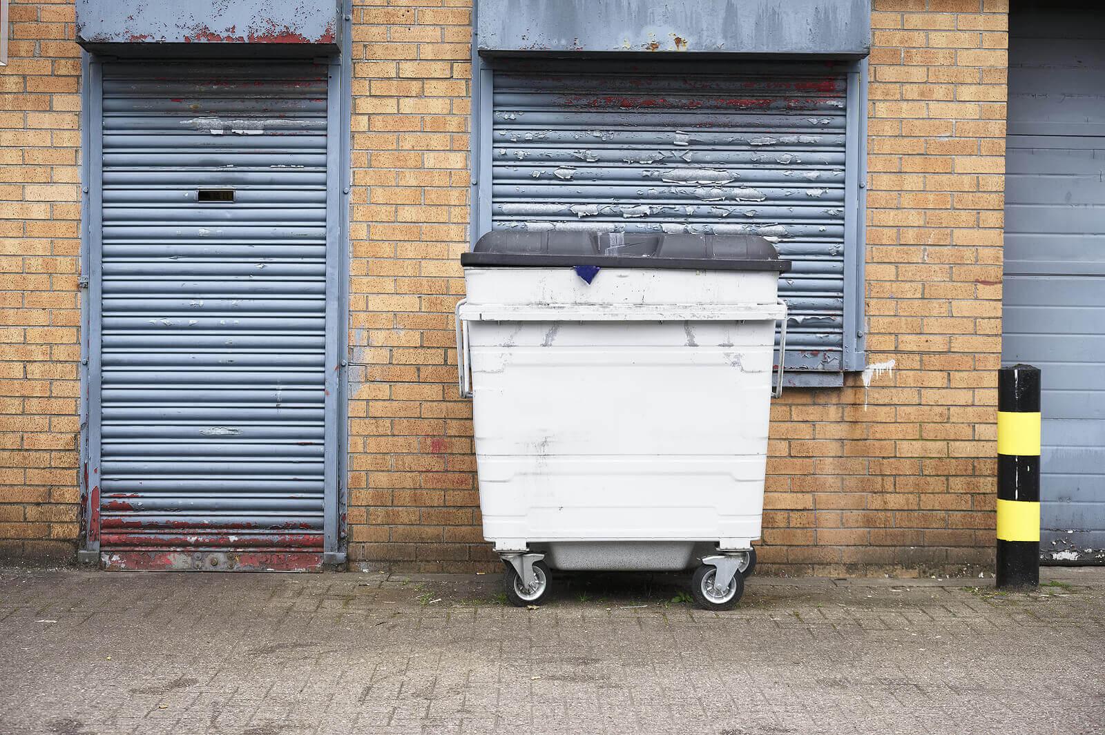 A white metal wheelie bin located in the street outside a shuttered shop window and doorway