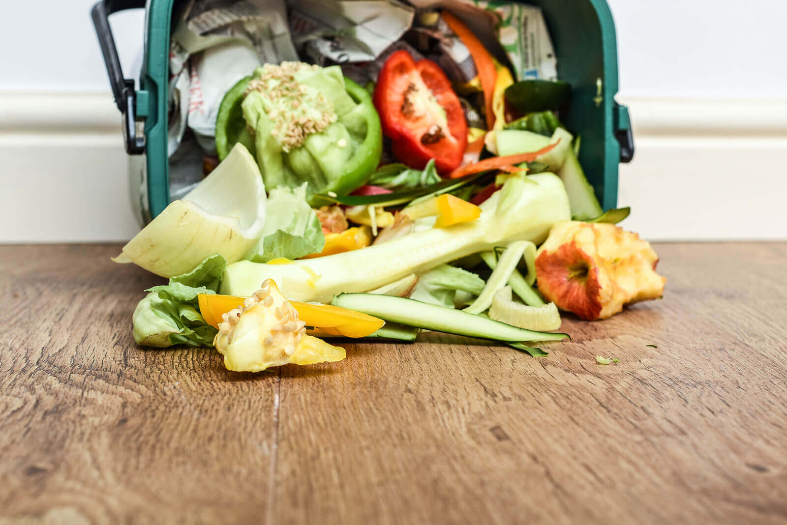 A green food waste caddy full of fruit and vegetable scraps, spilling onto a wooden floor