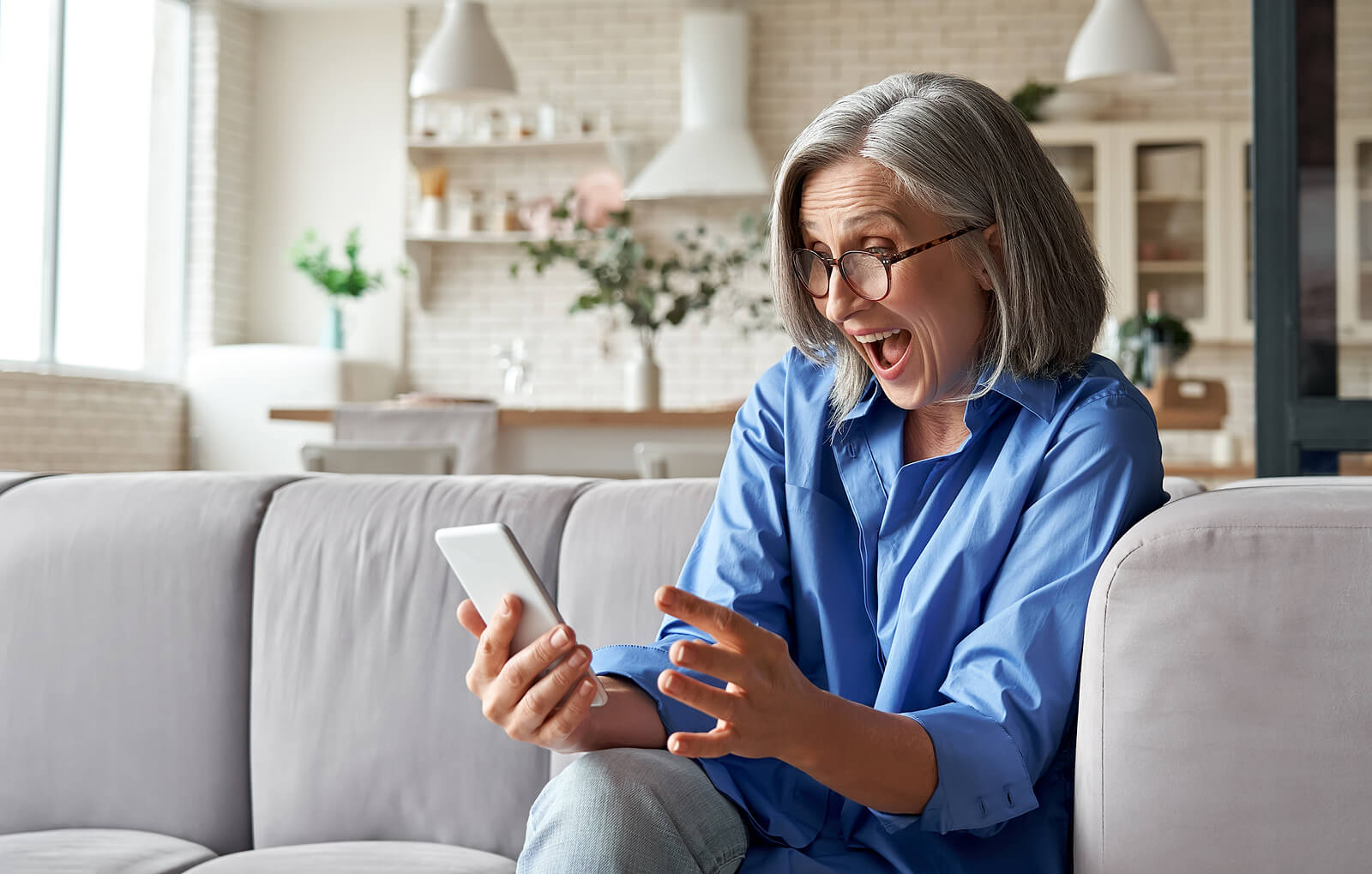 A happy mature woman with grey hair holding a mobile phone she has been gifted, sat on a sofa