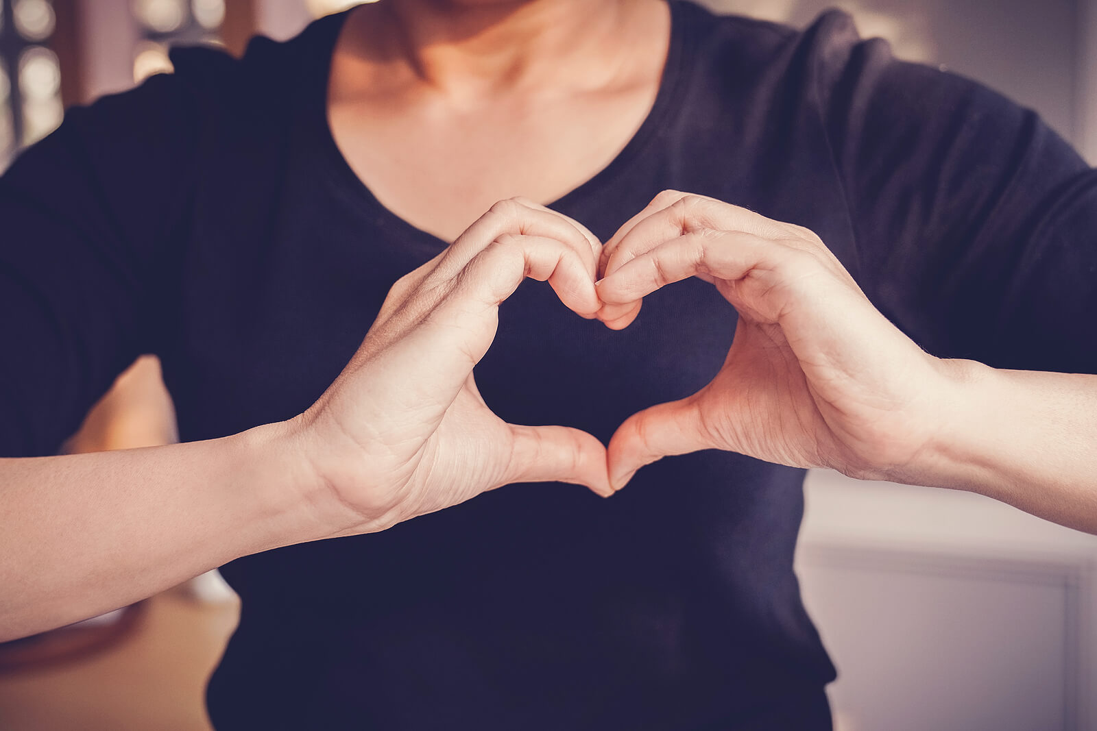 A woman making a heart with her hands infront of her chest, wearing a black t-shirt
