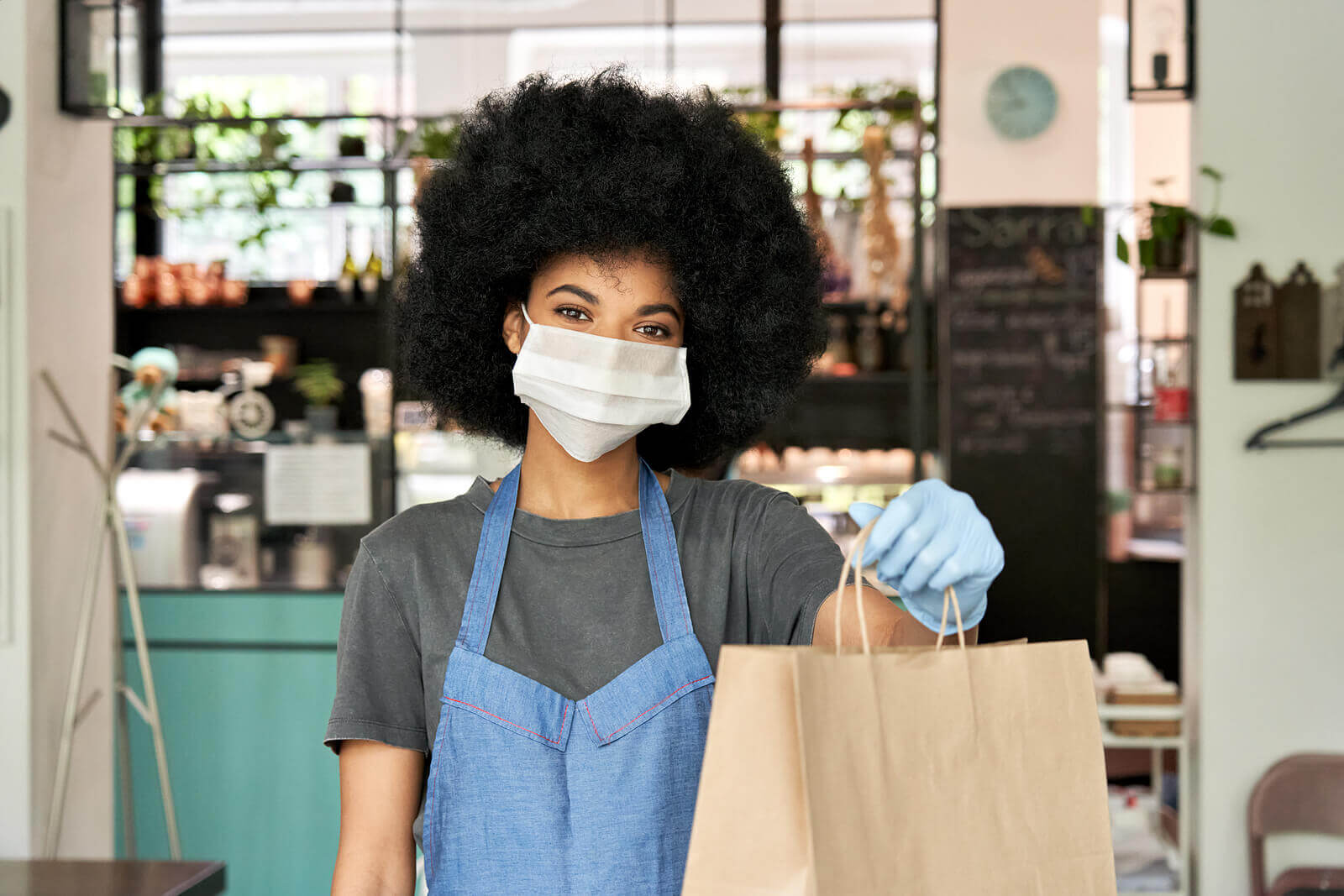 A Black female cafe worker, wearing an apron and face mask, holding a bag of food