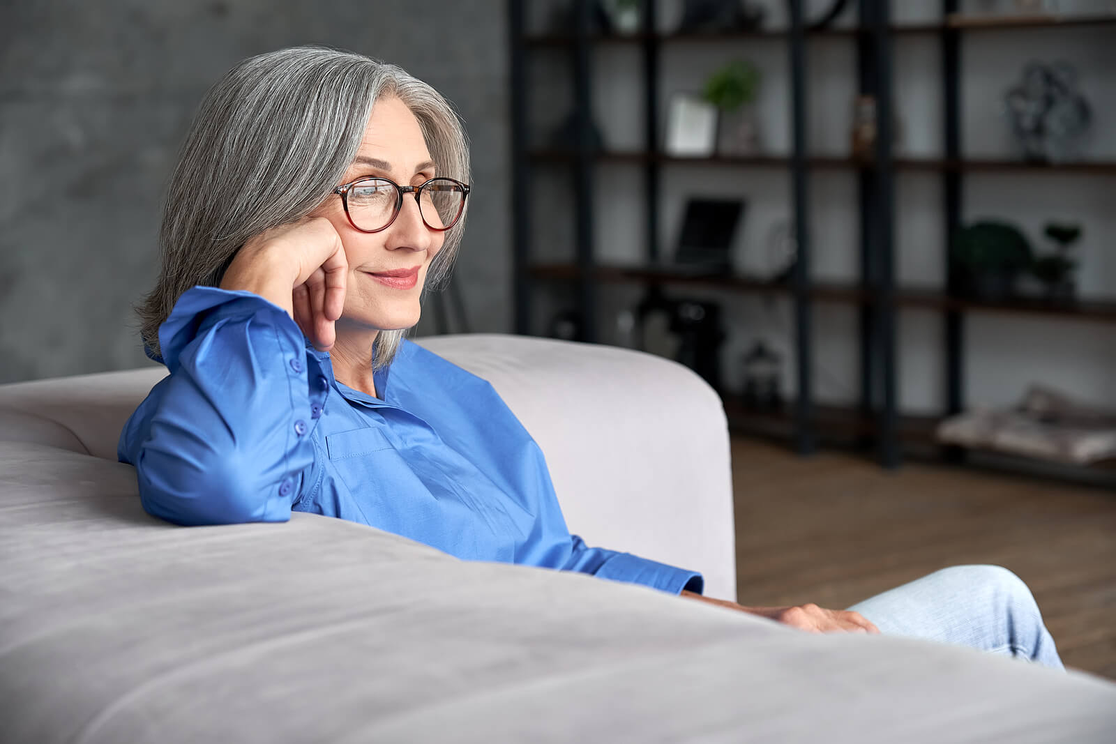 A mature white woman with grey hair sat on a sofa, wearing glasses and a blue top