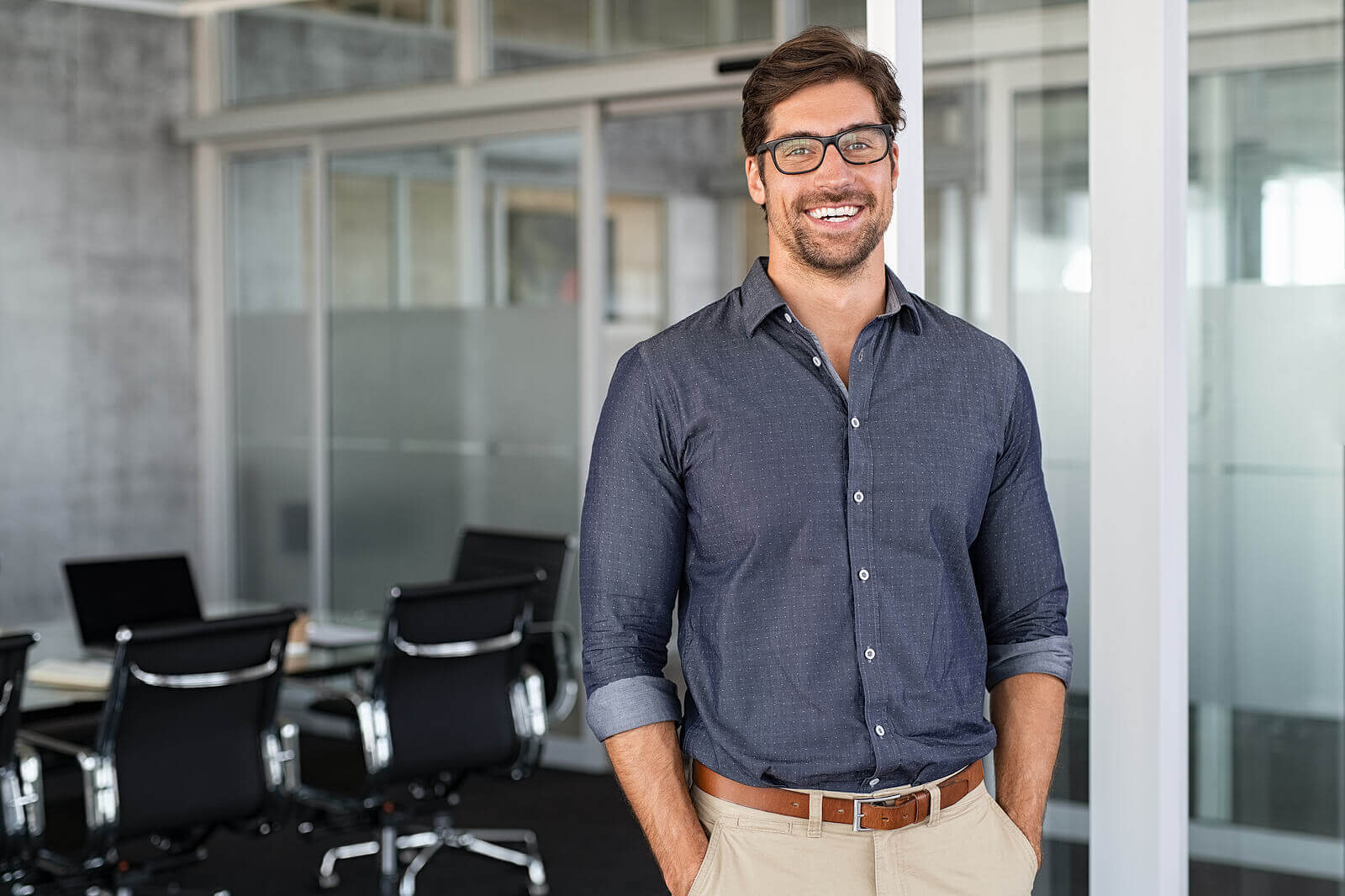 A happy white businessman stood in his office wearing glasses and a blue shirt